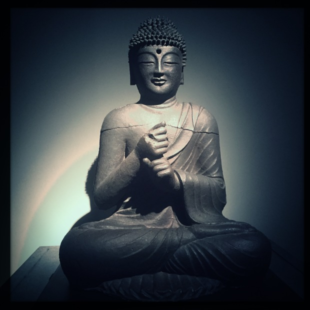 "Square photograph of an ancient Korean bronze Buddha statue, he is making the Bodhyangi mudra (hand gesture), also know as the ""Fist of Wisdom"""